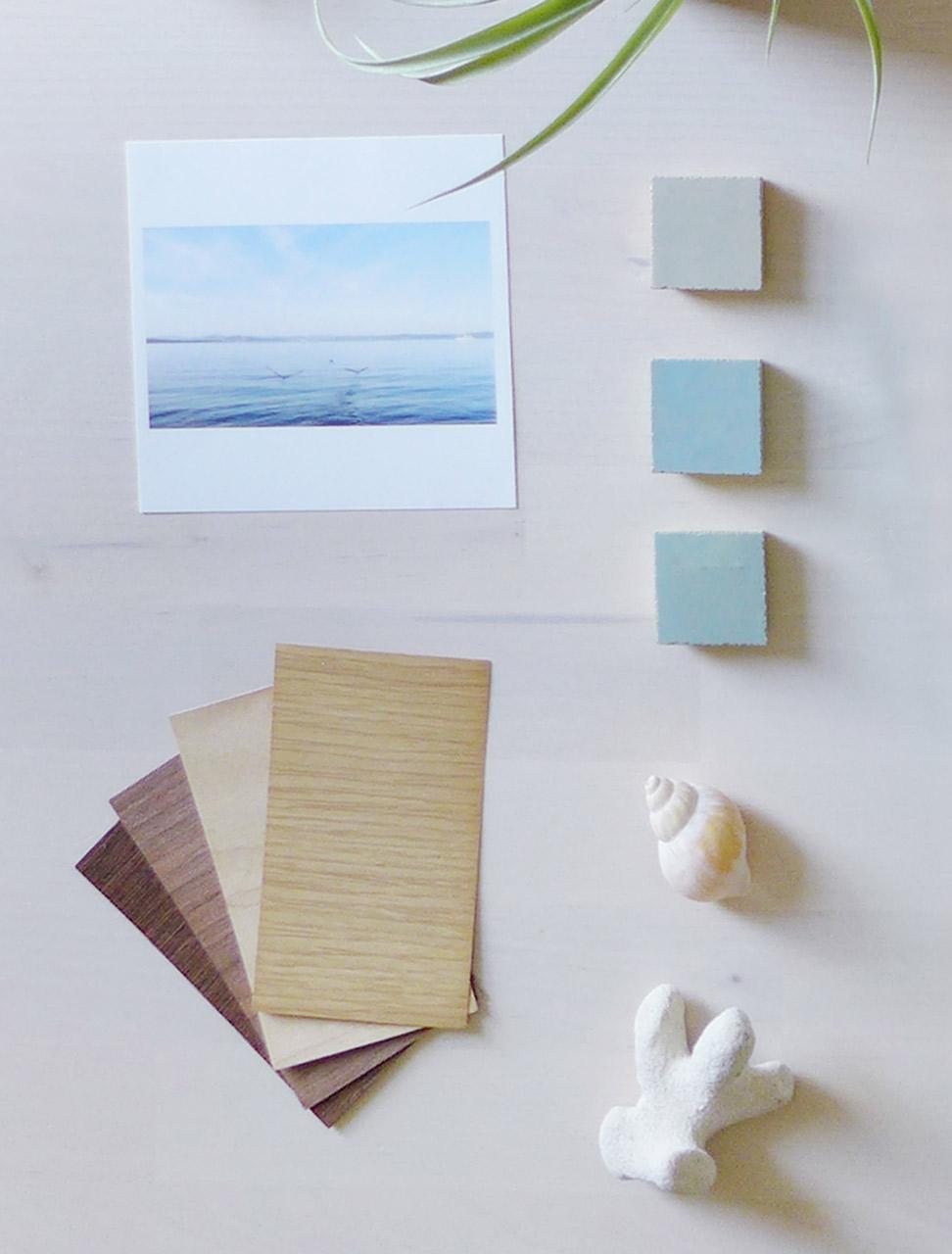 Illustration. Des échantillons de bois et de zelliges, un coquillage et du corail, une photo de la mer avec deux oiseaux prenant leur envole, sont disposés sur un fond en bois clair très nature.