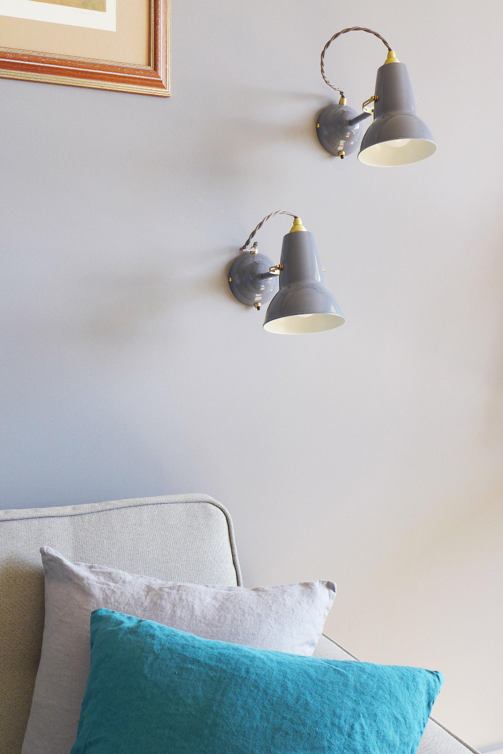 Détail de deux lampes en appliques Anglepoise posées sur un mur gris au-dessus d'un canapé.