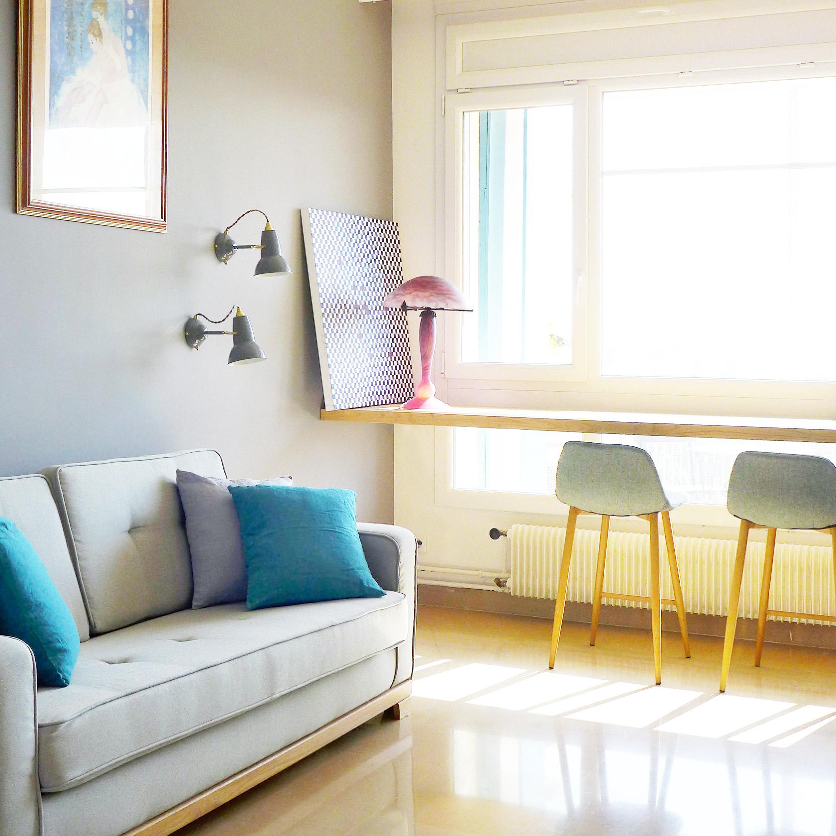 Un plan de travail prend place devant la fenêtre en guise de bureau. Un canapé convertible donne à cette chambre des airs de salon.