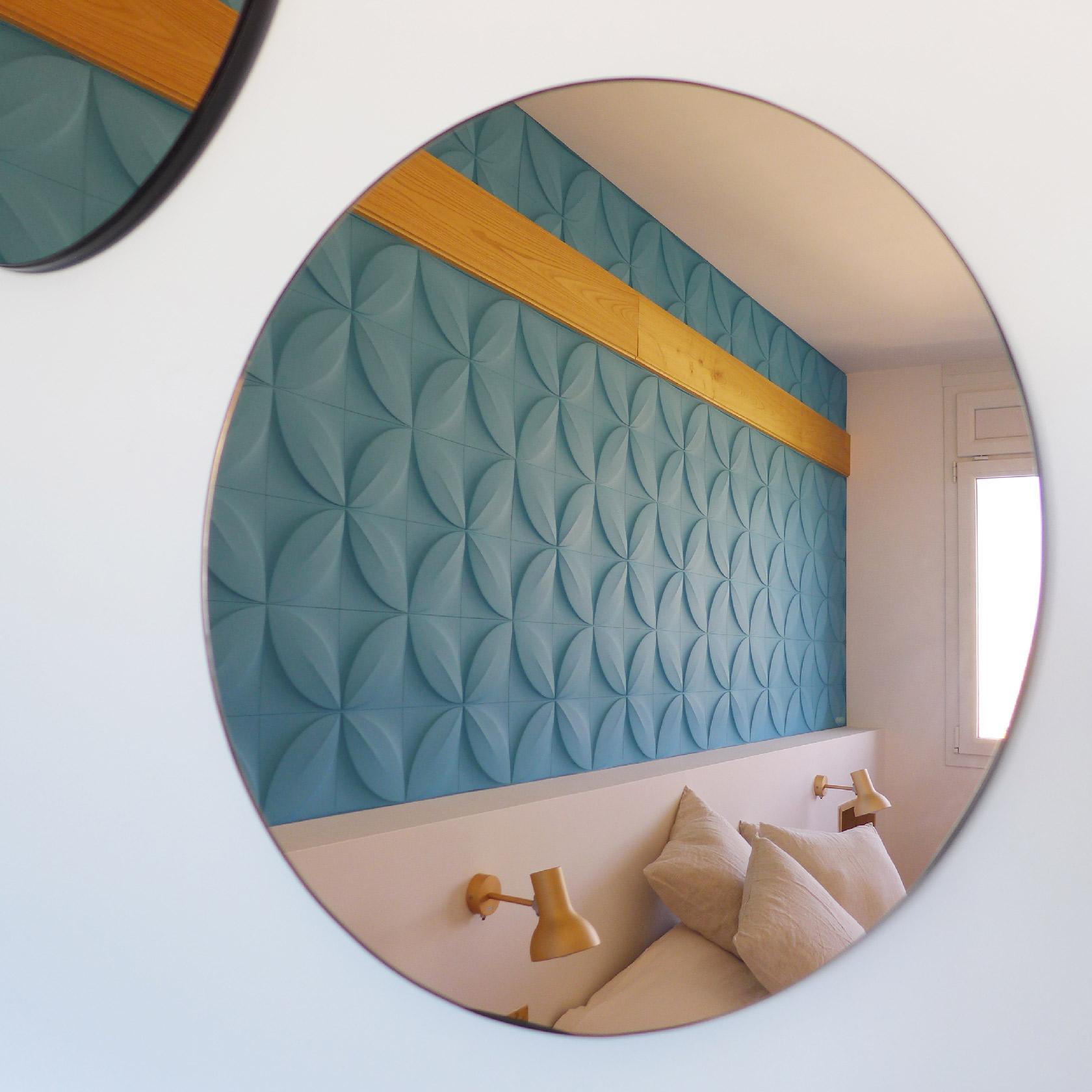 Au-dessus de la commode, trois miroirs ronds cuivrés.
