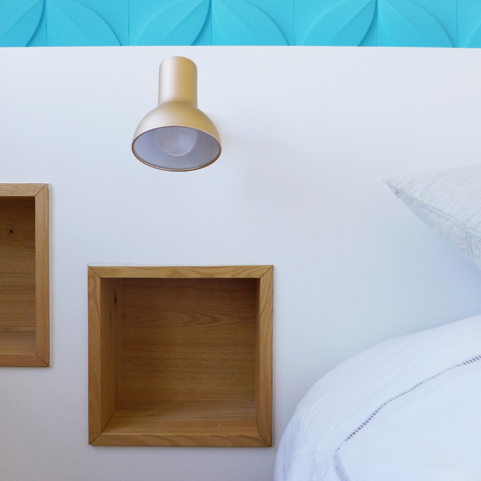 Dans la tête de lit sur mesure, des niches murales servent de chevet.