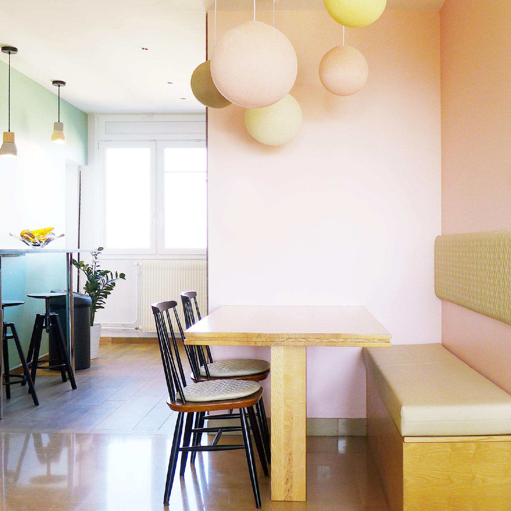 Coin-repas avec banquette. Mur rose pâle. Suspensions multiples colorées.