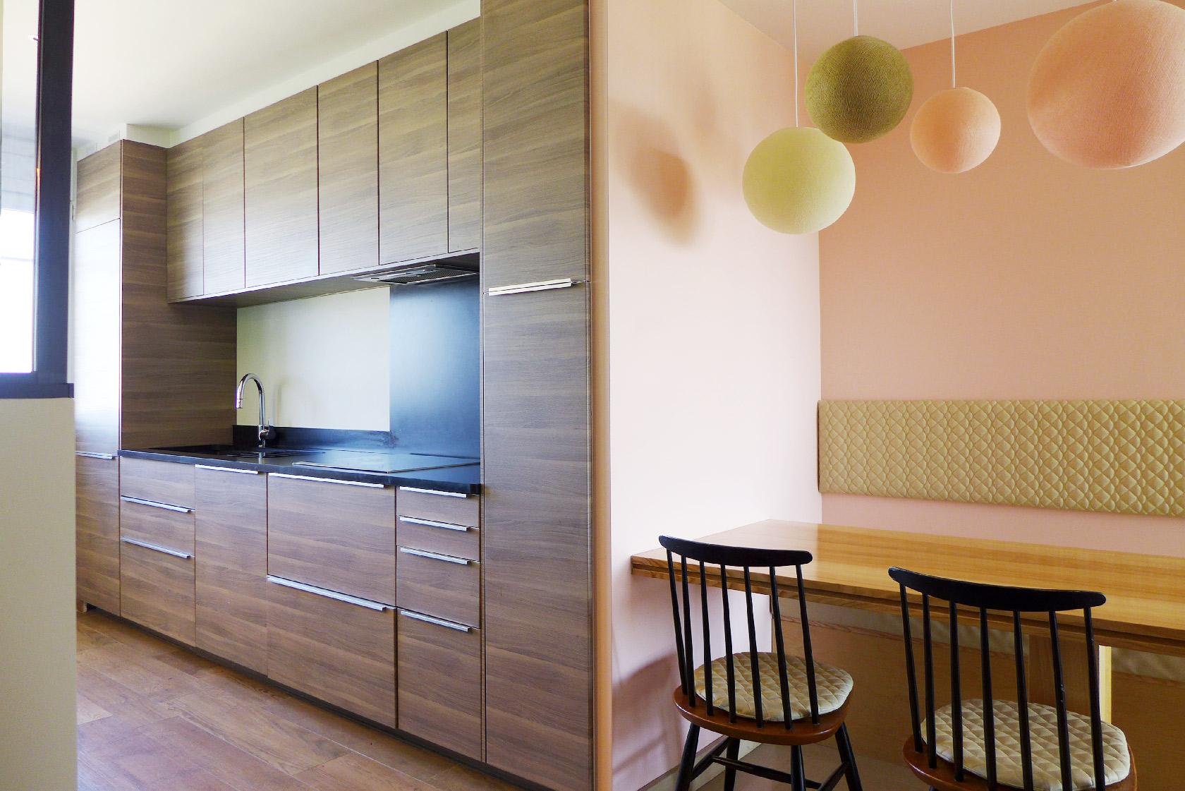 Vue d'une cuisine contemporaine. façades en bois foncé. Coin-repas avec banquette. Mur rose pâle. Suspensions multiples colorées.