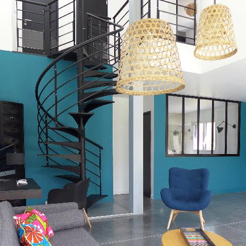 Réalisation du studio d'architecture et de décoration Skéa Designer. Prestation d'aménagement et de décoration d'une maison achetée sur plan. Vue d'un salon et d'un escalier hélicoïdal noir. Mur bleu paon.