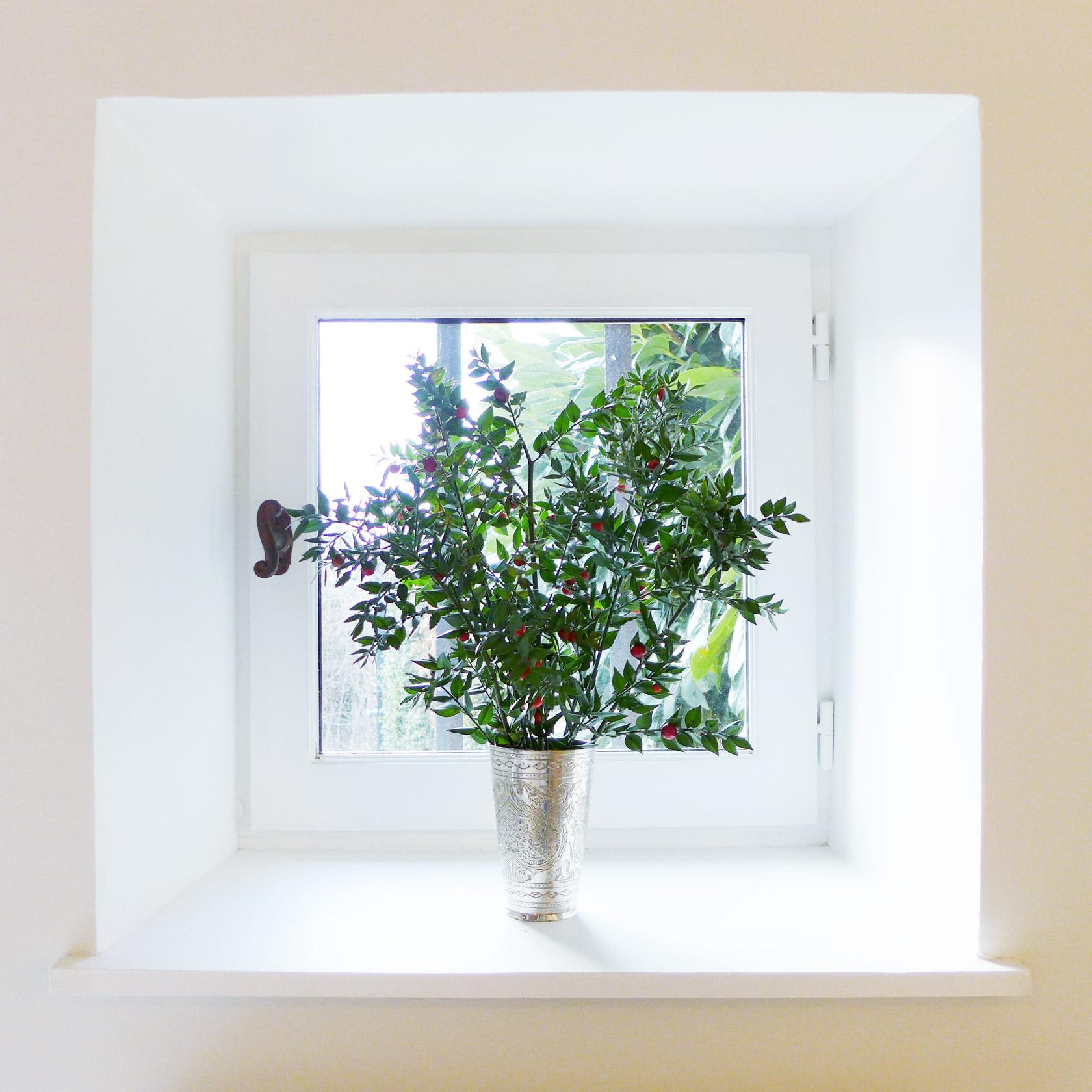 Réalisation du studio d'architecture et de décoration Skéa Designer. Zoom sur la fenêtre et son vase agrémenté d'un bouquet de feuillage.