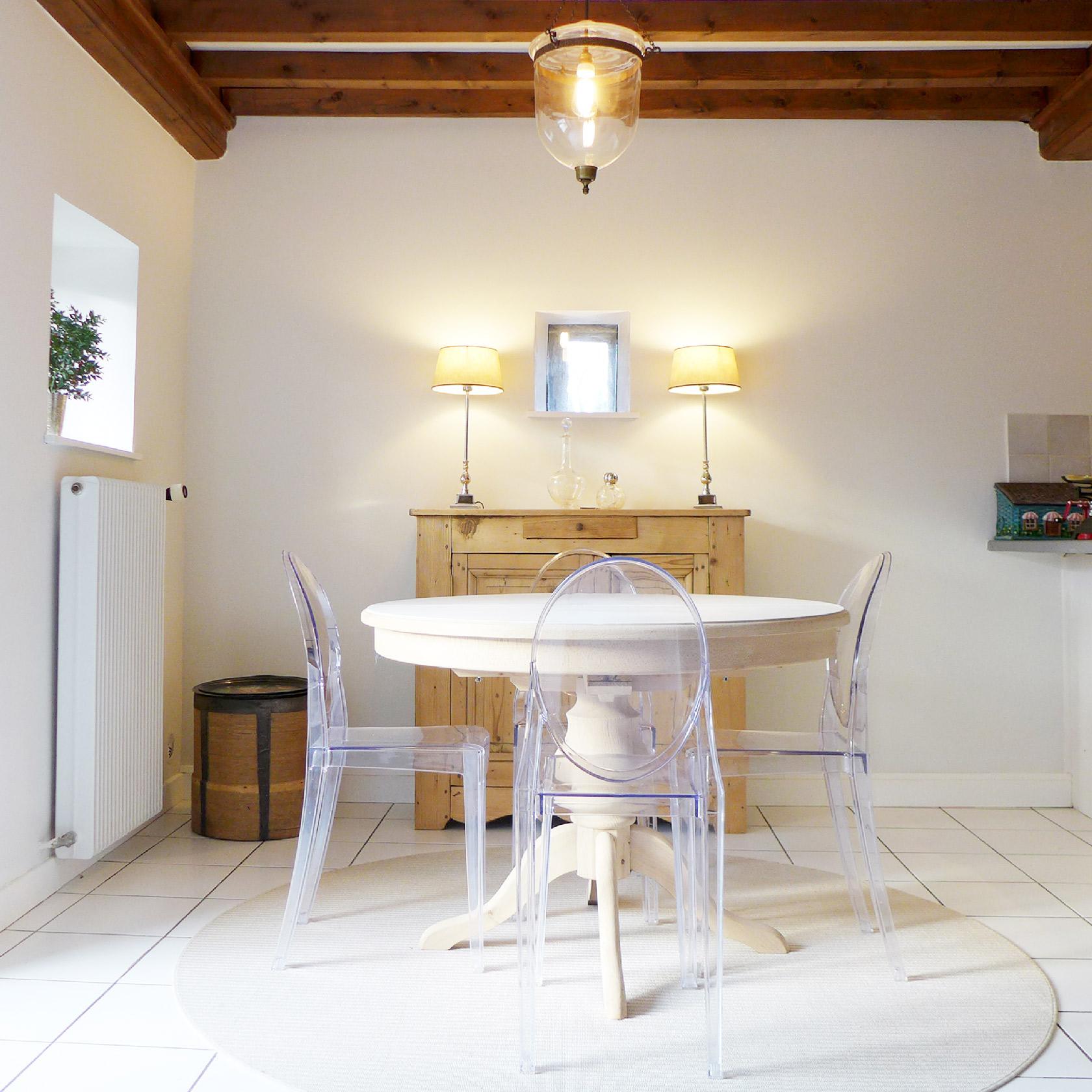 Réalisation du studio d'architecture et de décoration Skéa Designer. Dans la salle à manger, les meubles anciens ont été sablés pour un rendu très lumineux, les chaises Ghost de Starck apportent une touche de modernité. Les poutres apparentes donnent du cachet.