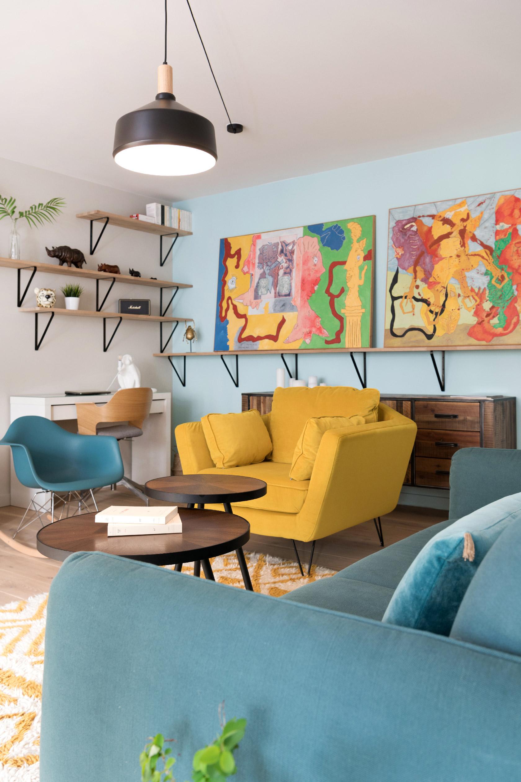 Le petit salon est quant à lui très coloré avec son canapé bleu canard et son fauteuil jaune.