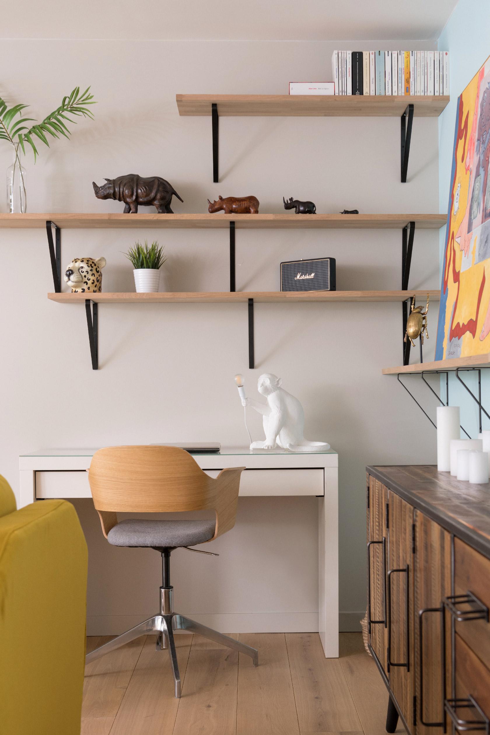 Le bureau blanc est surplombé d'une lampe singe Seletti et d'étagères. Un vase en forme de tête de léopard, une enceinte Marshall et une famille de Rhinocéros décorent les étagères murales.