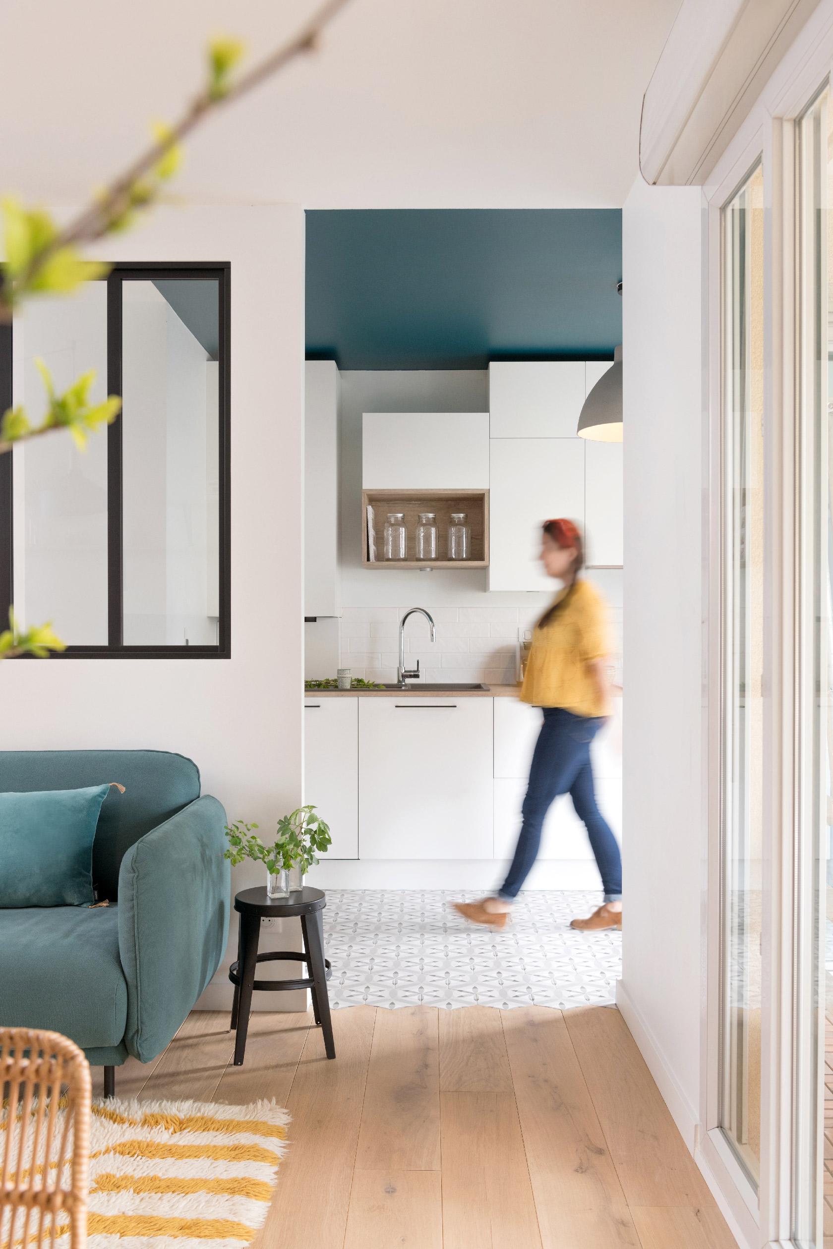Derrière la verrière et le canapé du salon, la cuisine blanche avec son plafond coloré bleu. Une silhouette floutée illustre la notion de circulation.