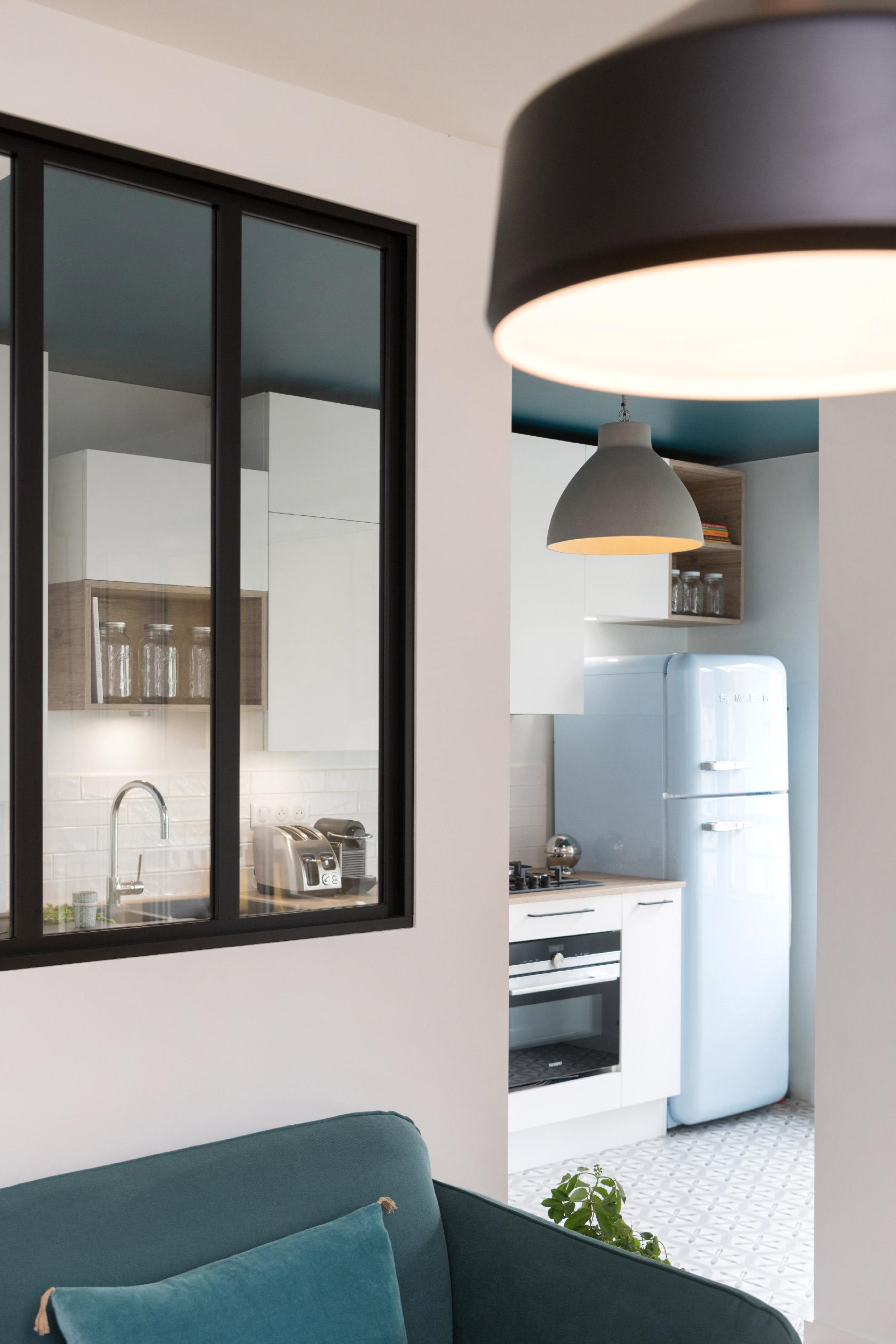 Derrière la verrière noire, un plafond coloré bleu paon et une cuisine aux façades blanches.