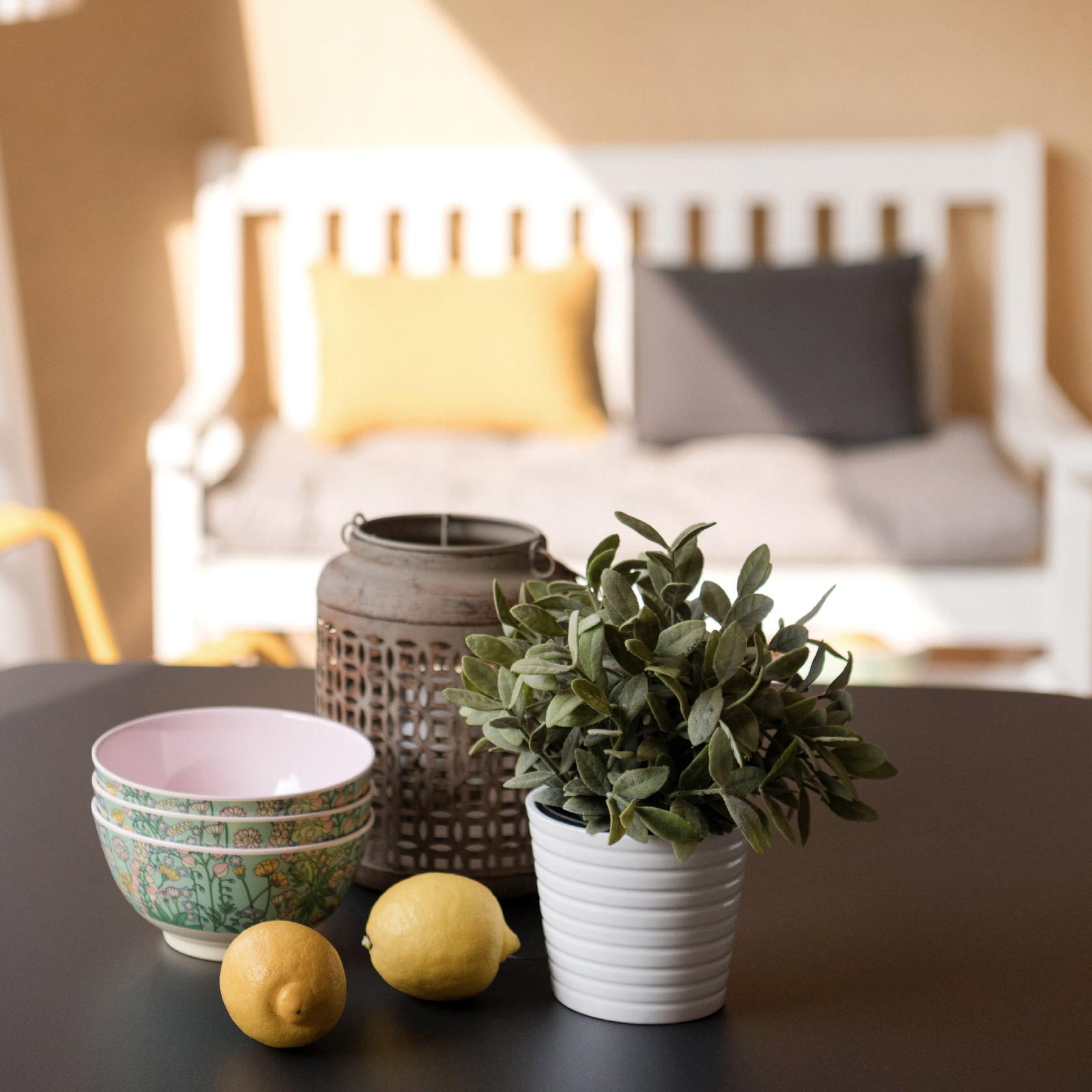 La terrasse comprend un banc en bois blanc et ses coussins en lin, un fauteuil, une table et des chaises de la marque Fermob déclinés dans les tons de gris anthracite et jaune.