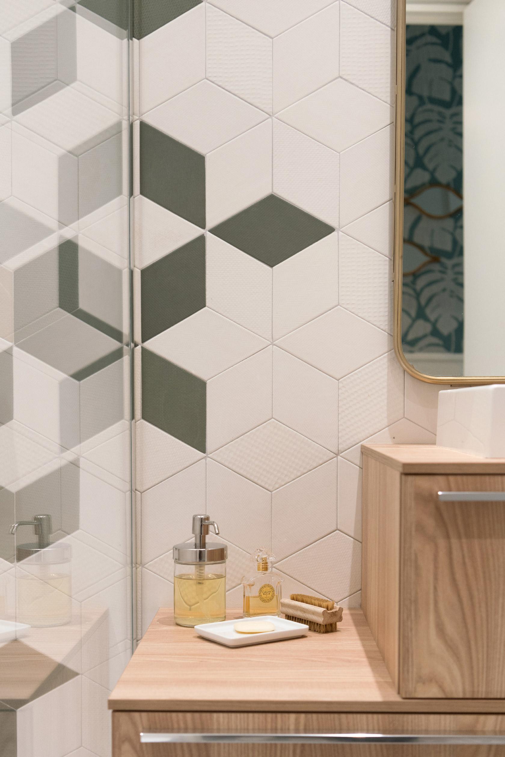 Les losanges du carrelage Mutina Tex se décline dans des teintes de vert, blanc et beige. La douche est séparée par un part douche épuré. La vasque comprend deux meubles posés en quinconce avec une vasque à poser et un miroir en laiton. Une salle de bain aveugle originale et atemporelle.