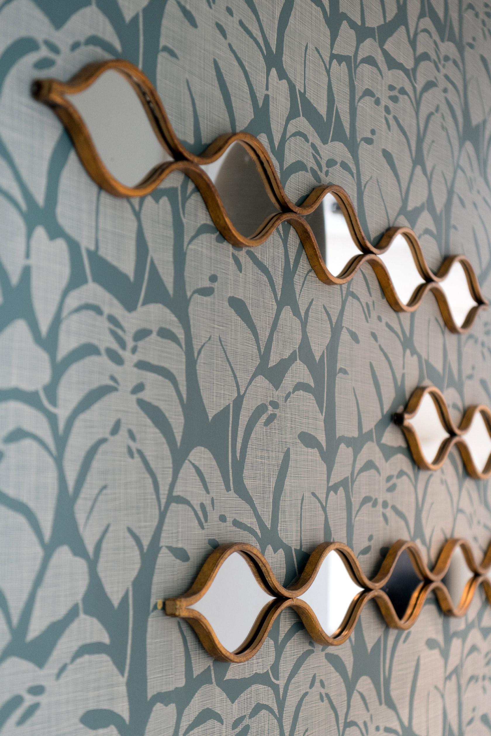 Les miroirs dorés apportent la touche finale au papier peint Missprint Guatemala et le dessin de ses feuilles de palmiers.