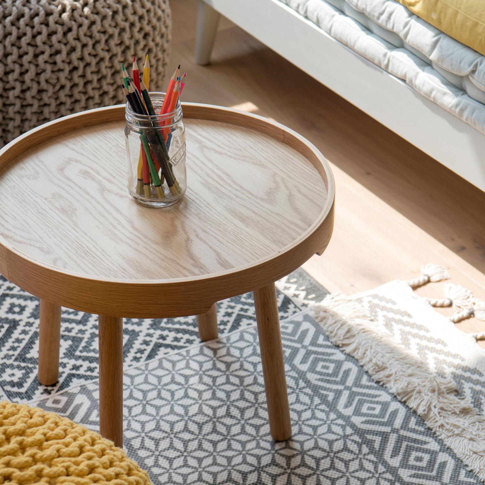 Une chambre d'enfant très bohème avec ses tables basses et ses tapis à motifs variés.