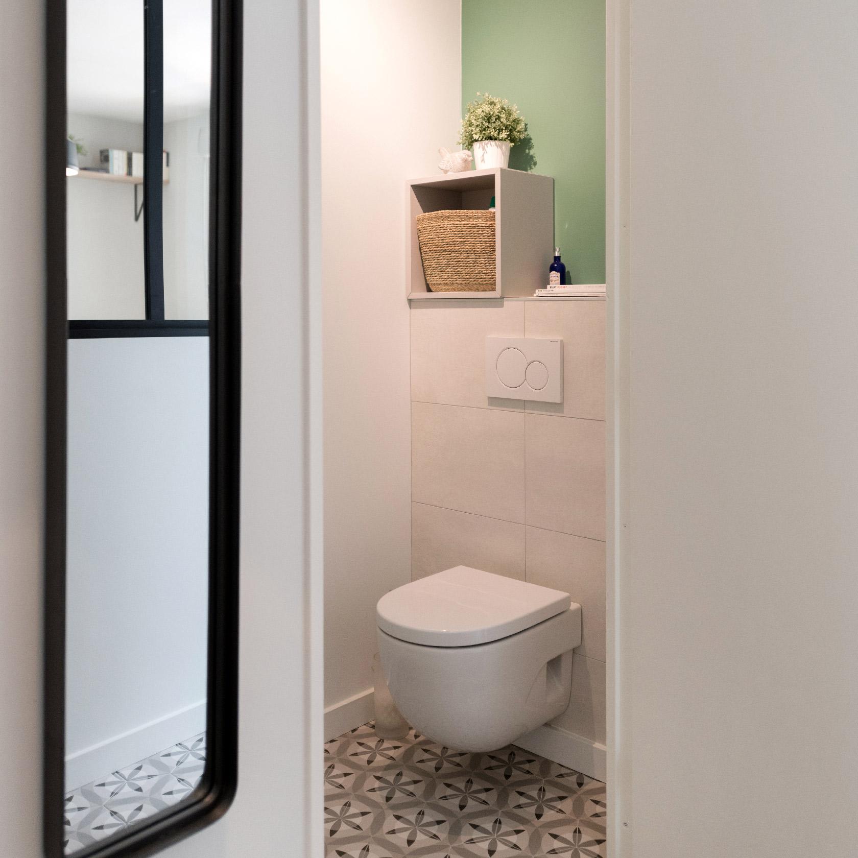 Le wc suspendu est carrelé tandis que l'arrière mur est peint en vert pour une touche de couleur. Une petite déco est posée sur la niche murale.