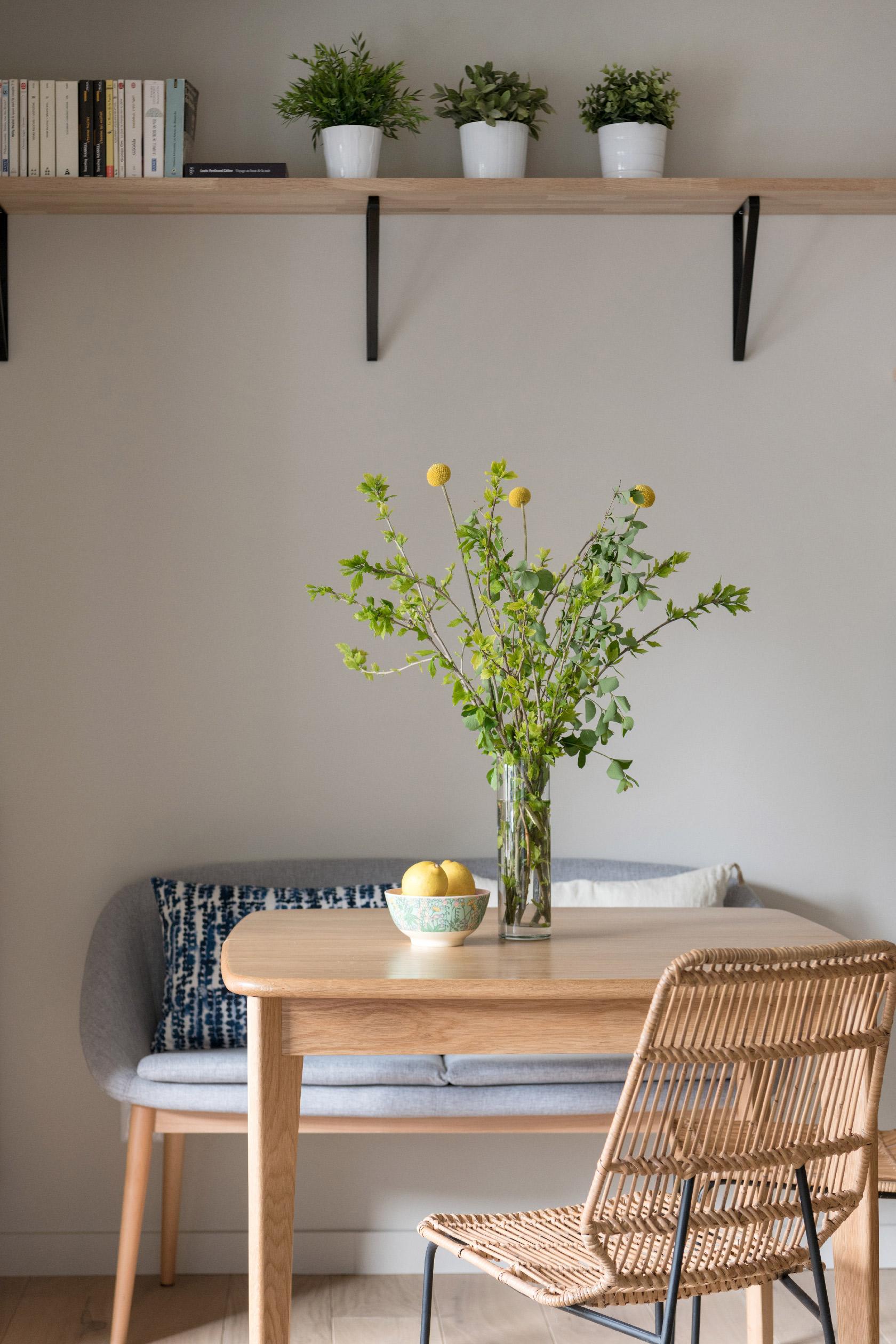 Le coin repas comprend une table extensible, deux chaises en osier, une causeuse et des coussins décoratifs.