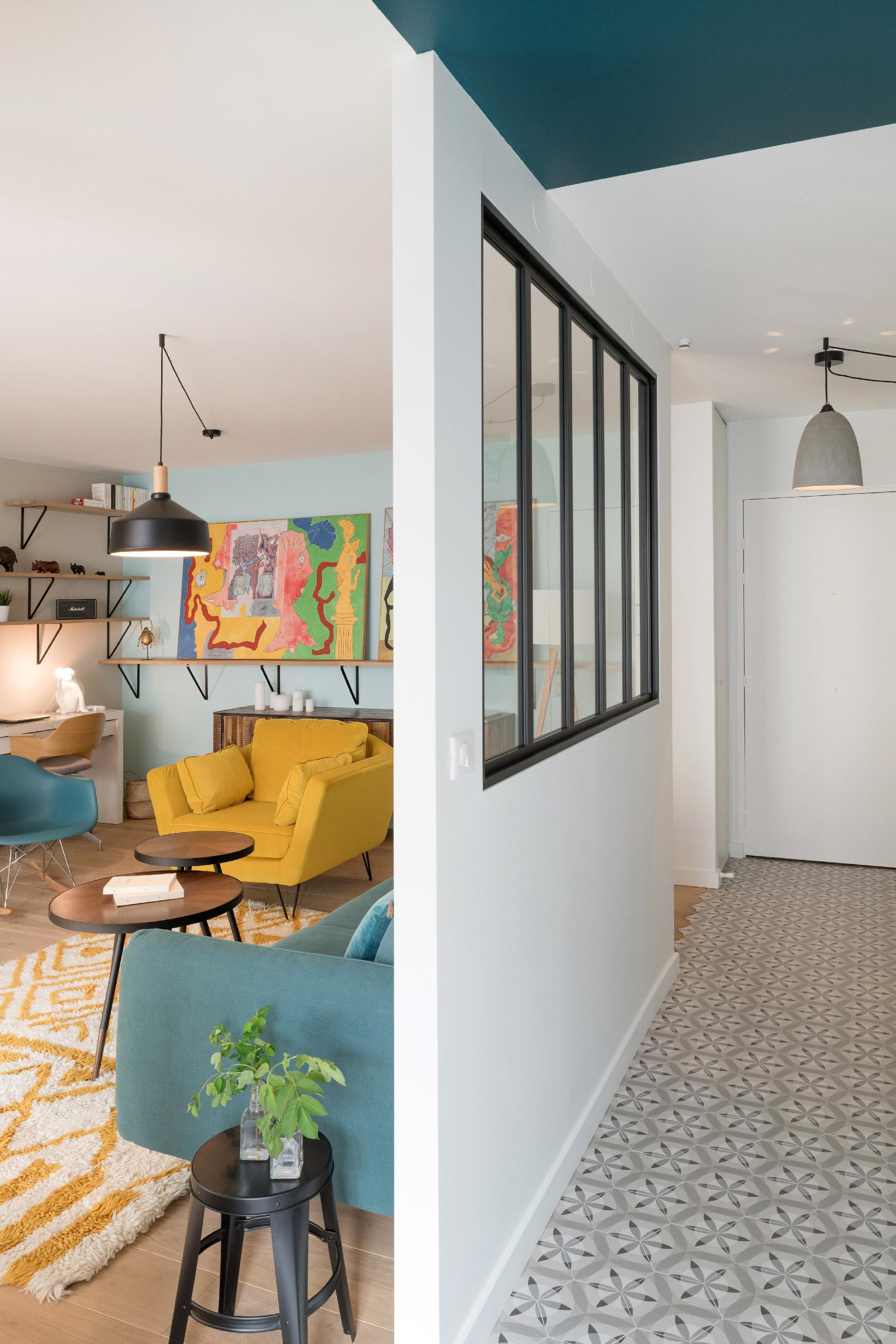 Entre le couloir et le salon, une verrière atelier laisse la lumière traverser.