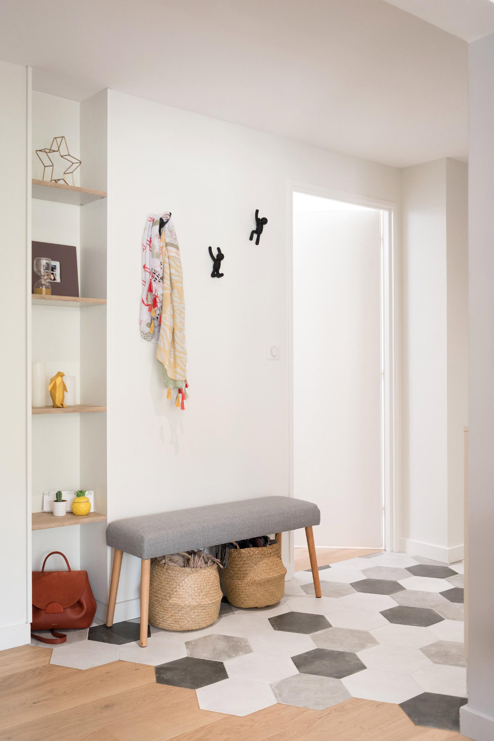 Un banc en bois avec un coussin d'assise, des panières et une étagère forment une belle entrée.