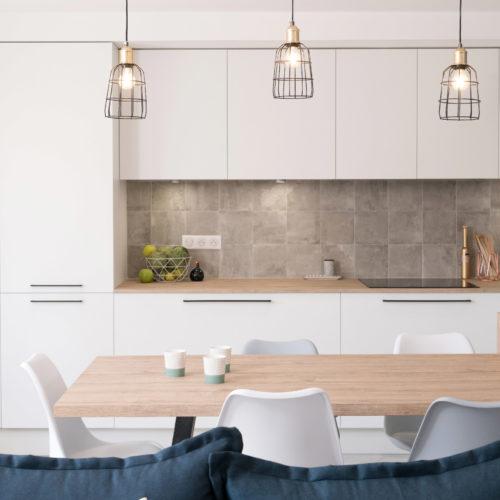 Derrière le canapé bleu, un îlot de cuisine avec table et bar, un long plan de travail entouré de deux façades. Une pièce de vie ultra tendance.
