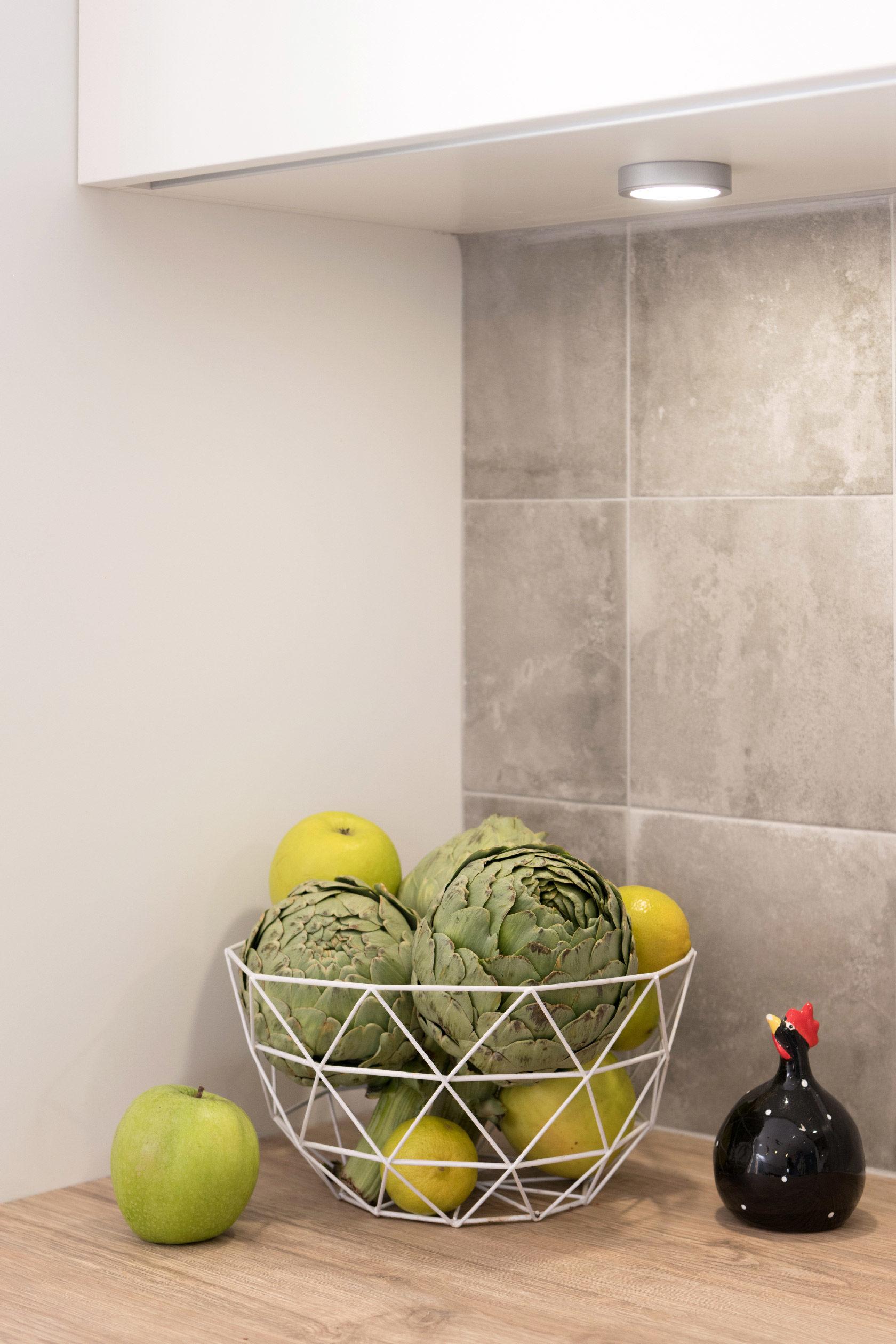 Un plan de travail en carrelage imitant un carreau de ciment gris, une façade de cuisine, une panière remplie d'artichauts. Une ambiance toute douce pour cette cuisine.