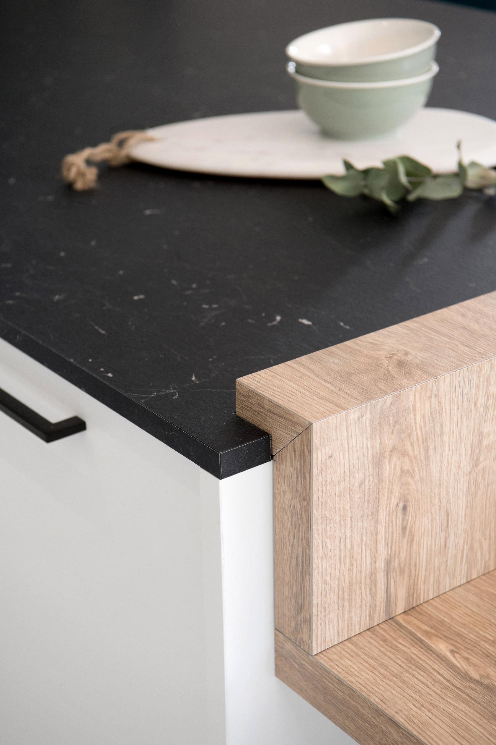 Détail d'un plan de travail imitant le marbre noir et de la jointure avec la table.