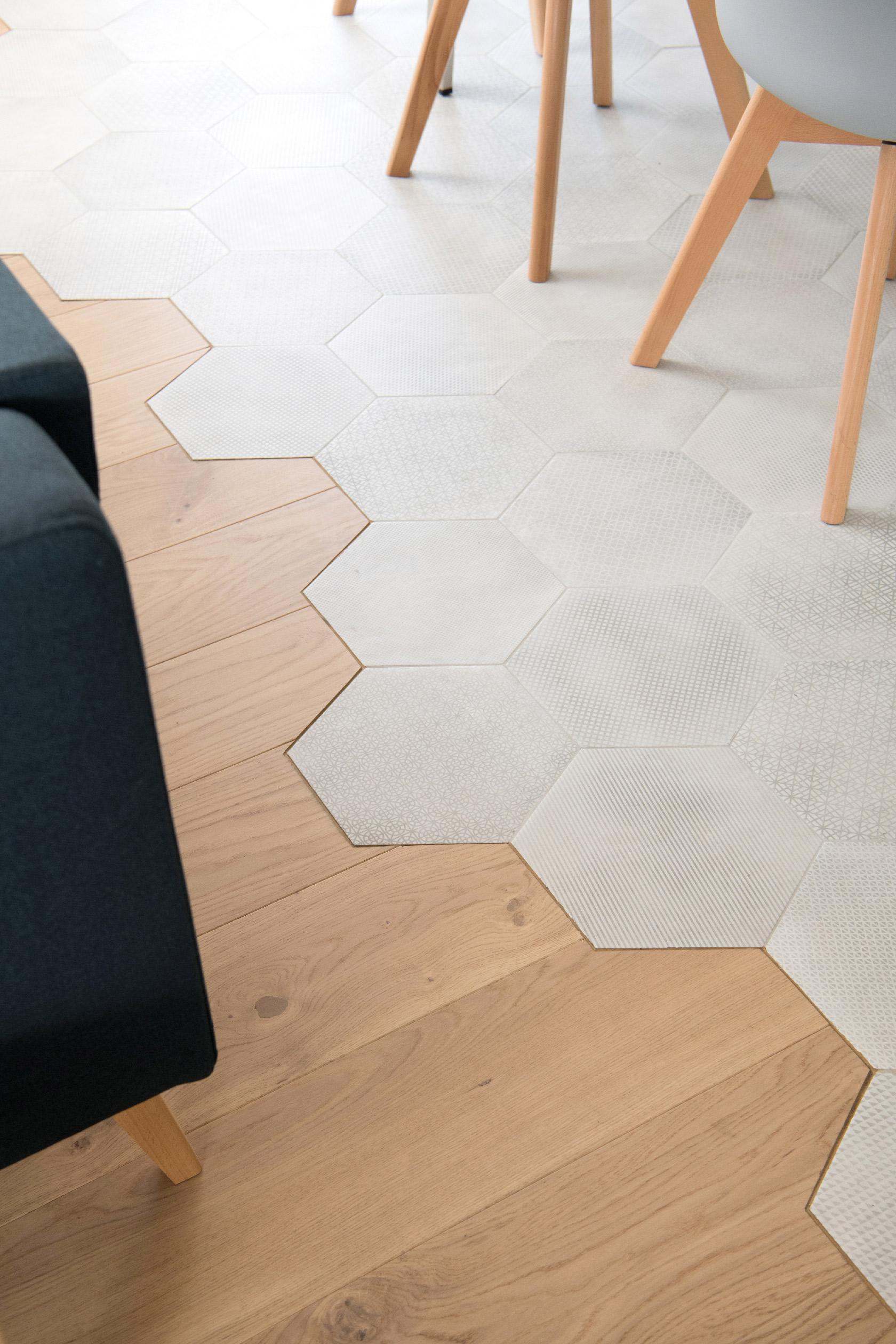 Au sol, la forme du carrelage imitant un carreau de ciment à motif gris au format hexagonal est épousée par la découpe du parquet en chêne clair.