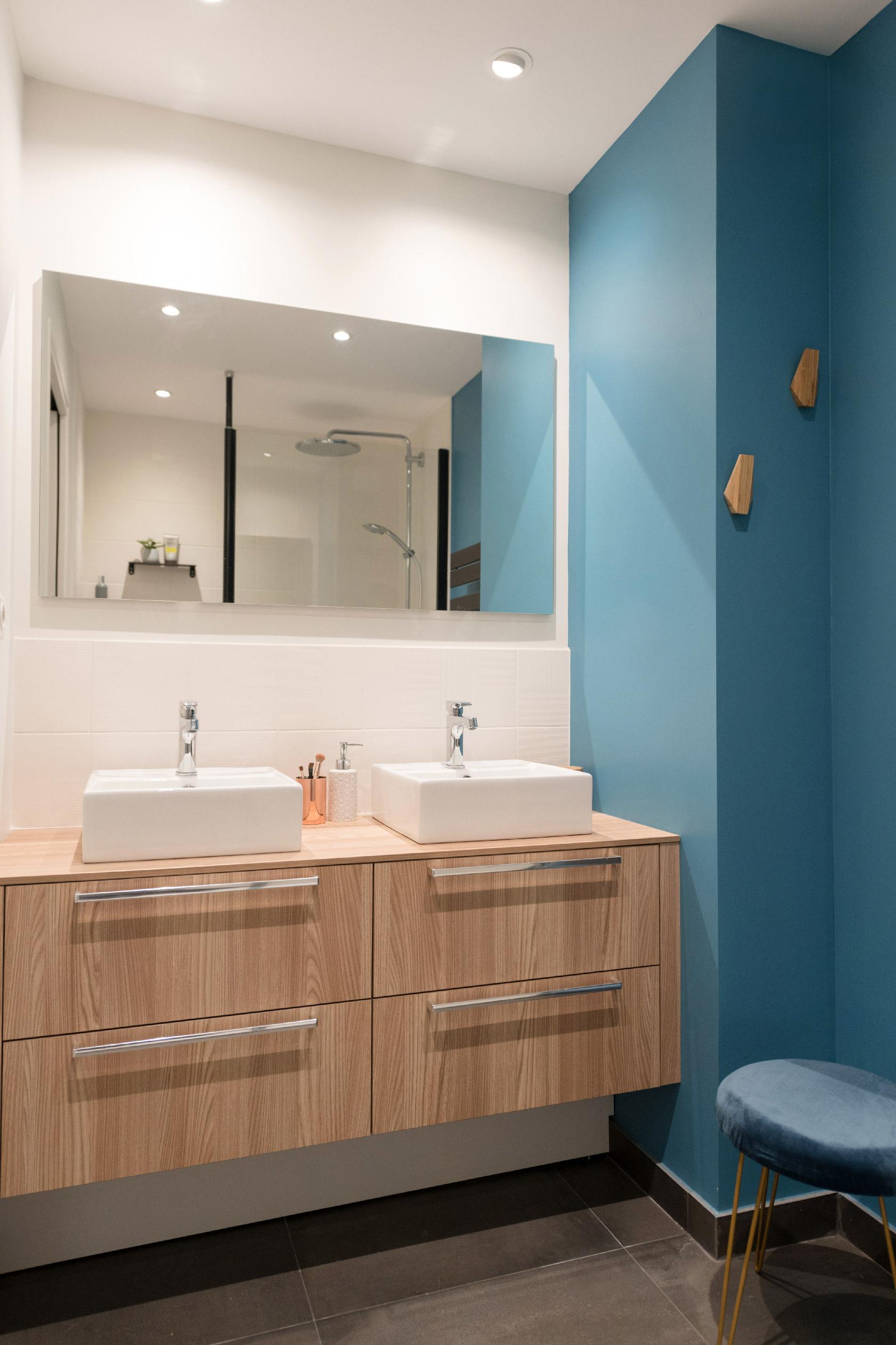 Deux vasques sont posées sur une vasque en bois mesurant 120 cm. Le tout est surplombé d'un grand miroir allongé. La faïence est blanche et un mur est peint en bleu. Une salle de bain originale et atemporelle.