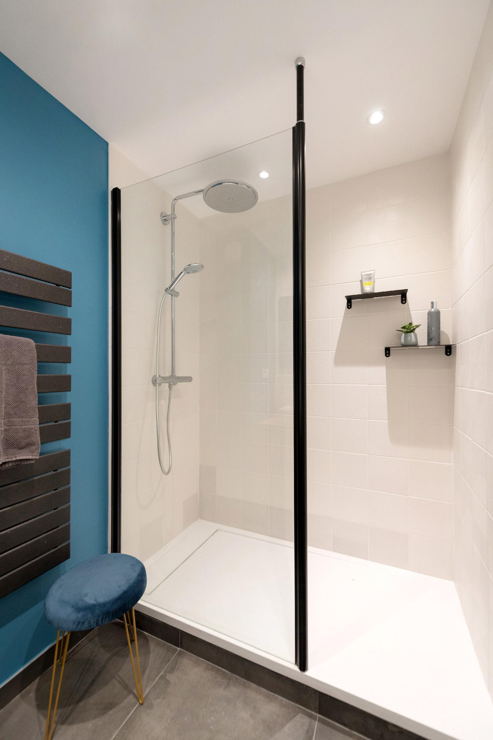 Une salle de douche contemporaine avec un mur bleu, un sèche serviette anthracite, un carrelage blanc et un part douche au cadre noir.