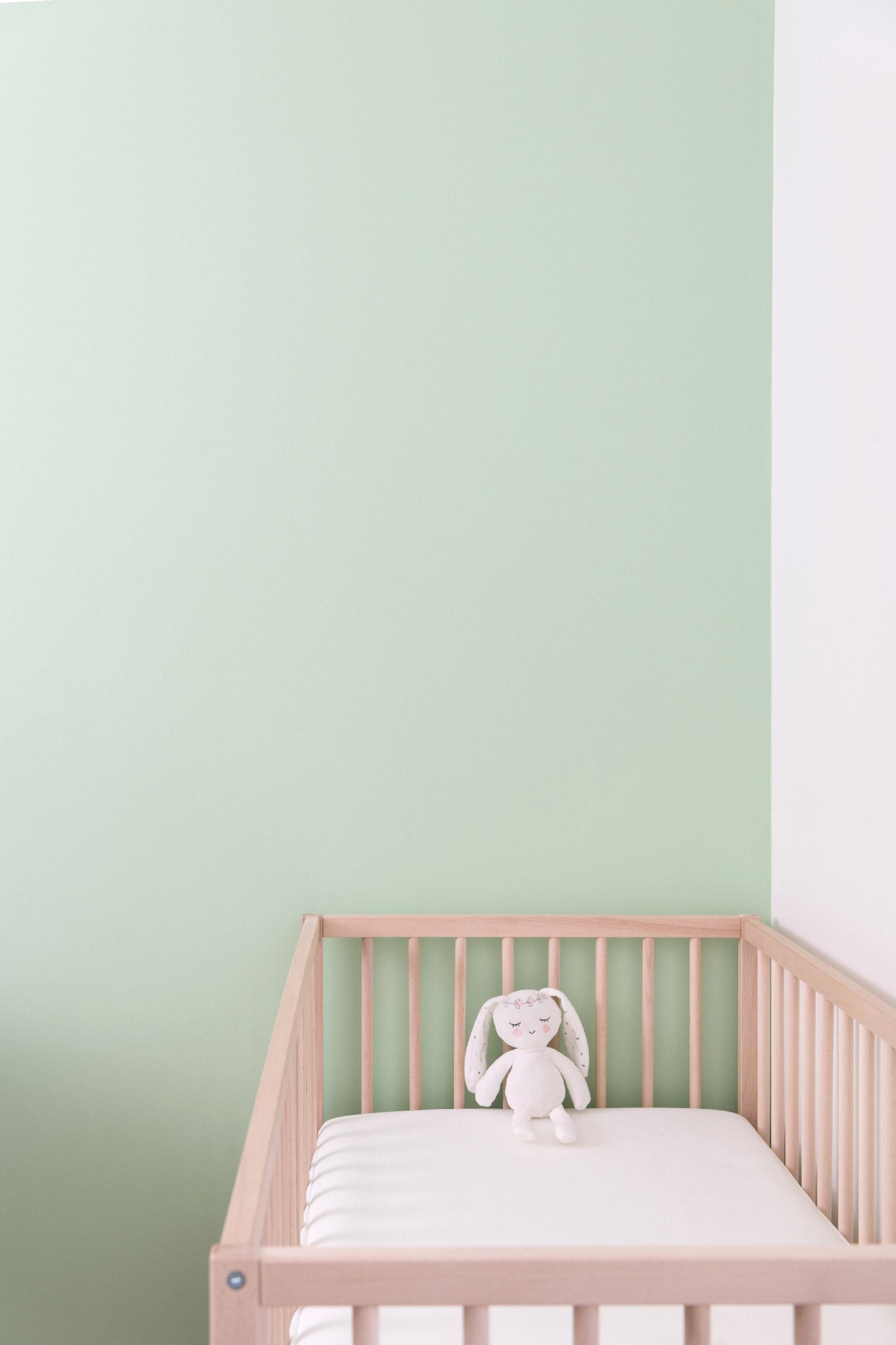 Un lit de bébé en bois clair est positionné devant un mur vert pastel.