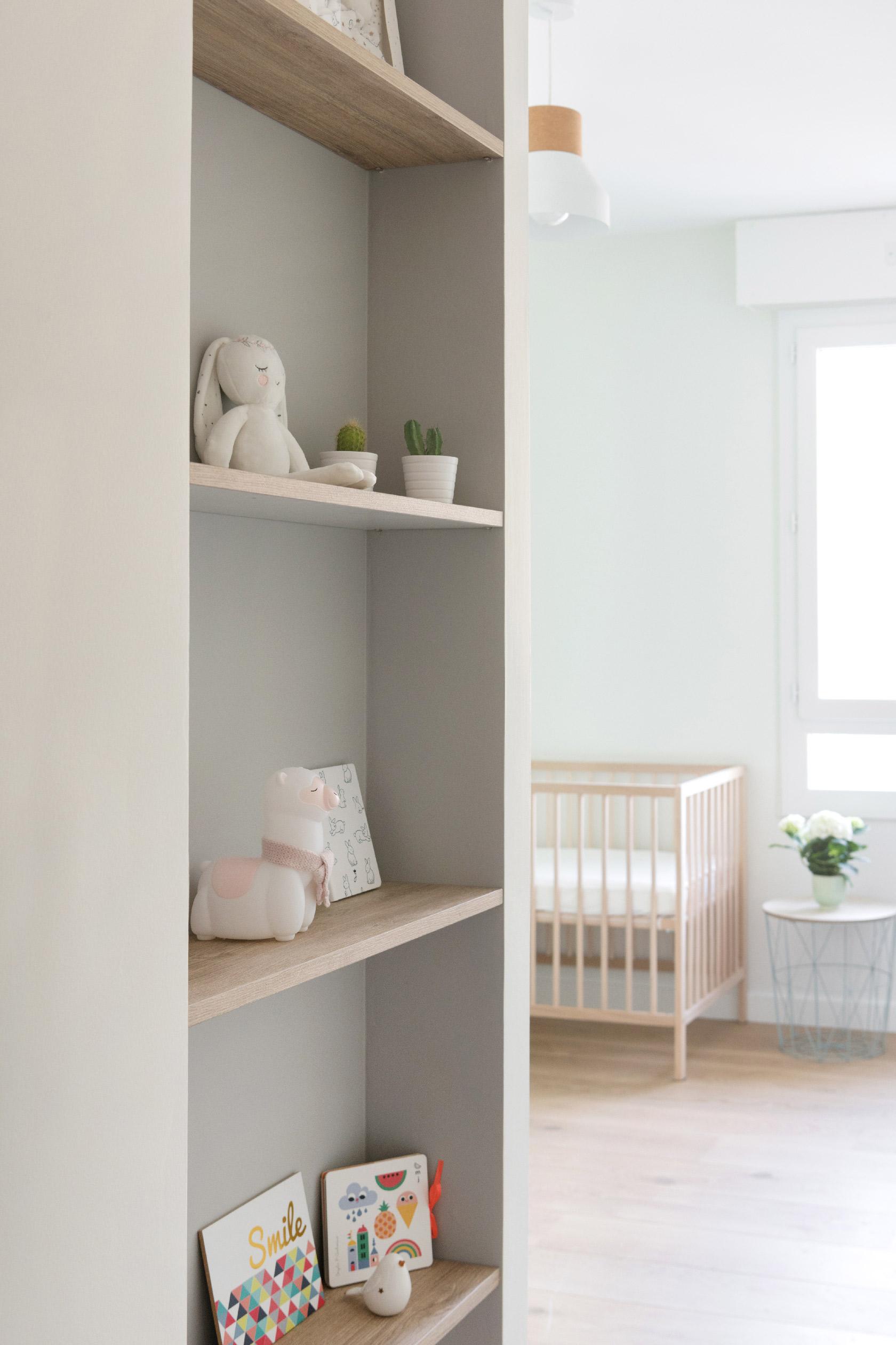 Dans l'entrée de la chambre de bébé, une étagère sur mesure en gris et bois.