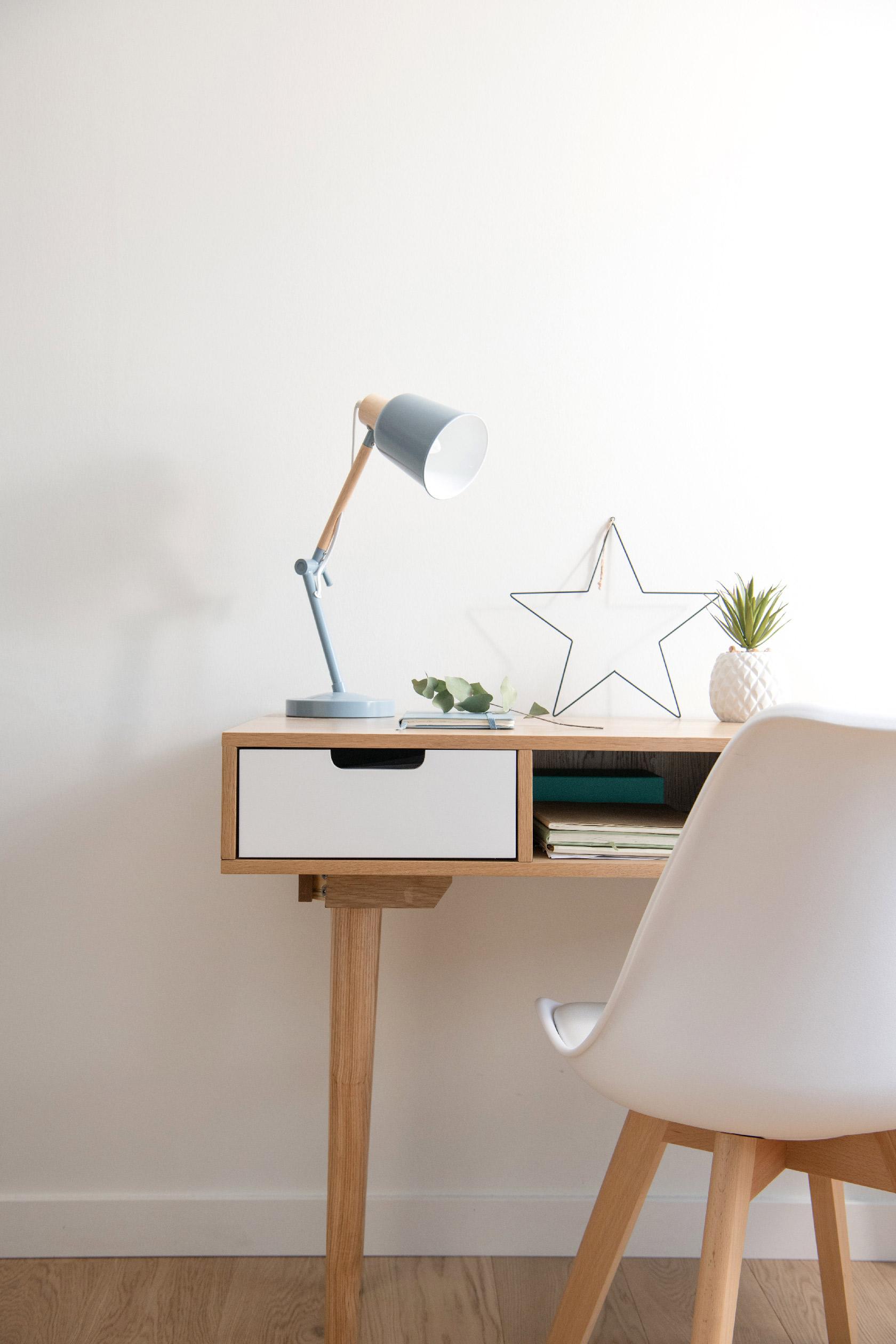 Un bureau de style scandinave prend place devant le mur blanc. Une déco très tendance.