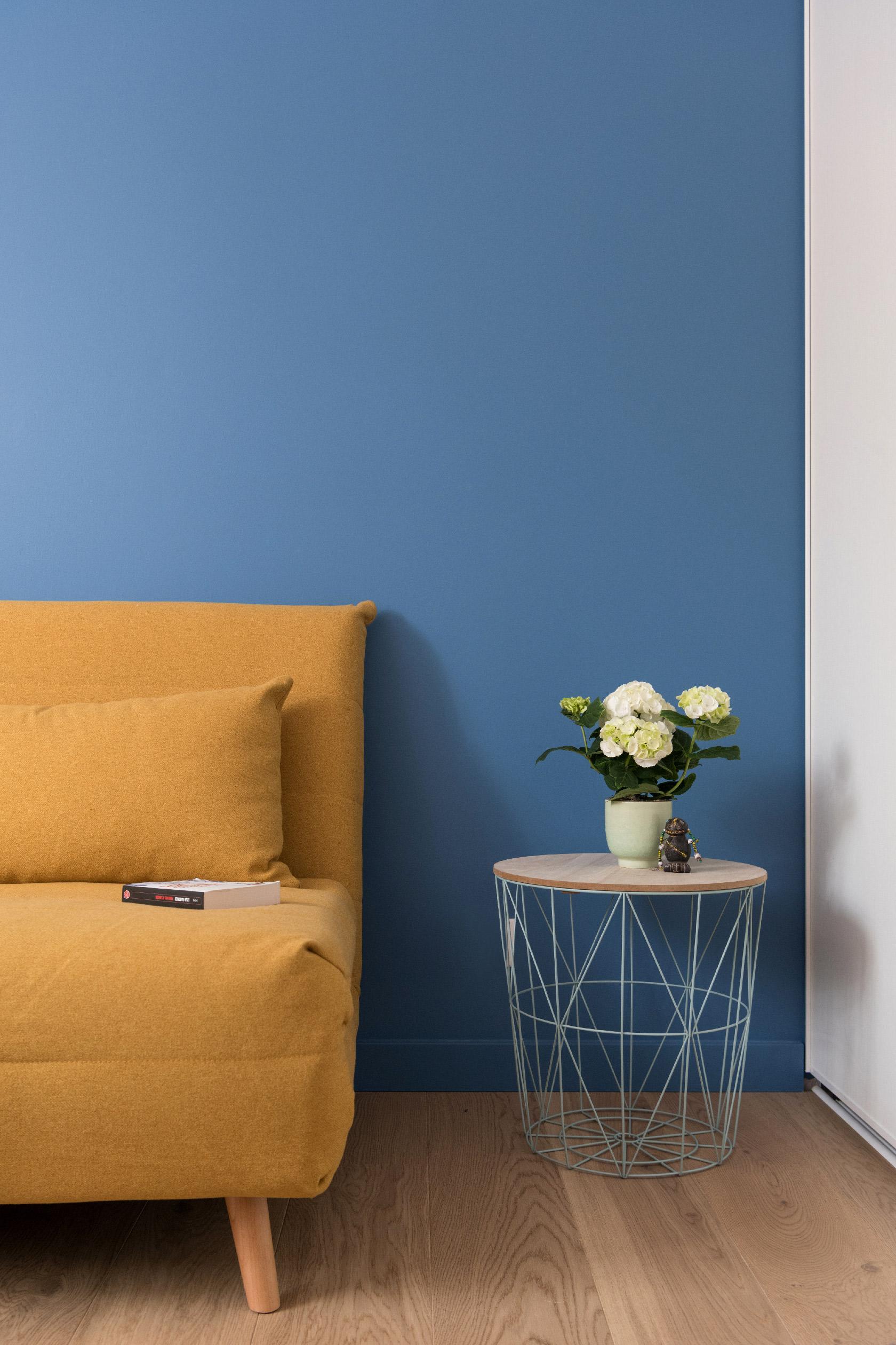 Devant un mur bleu, un canapé convertible jaune. Une chambre d'ami sobre et accueillante.