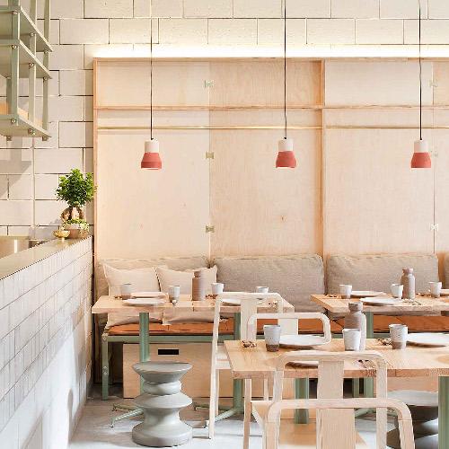 Les suspensions Ciment and wood éclairent un restaurant avec leur teinte orangée.