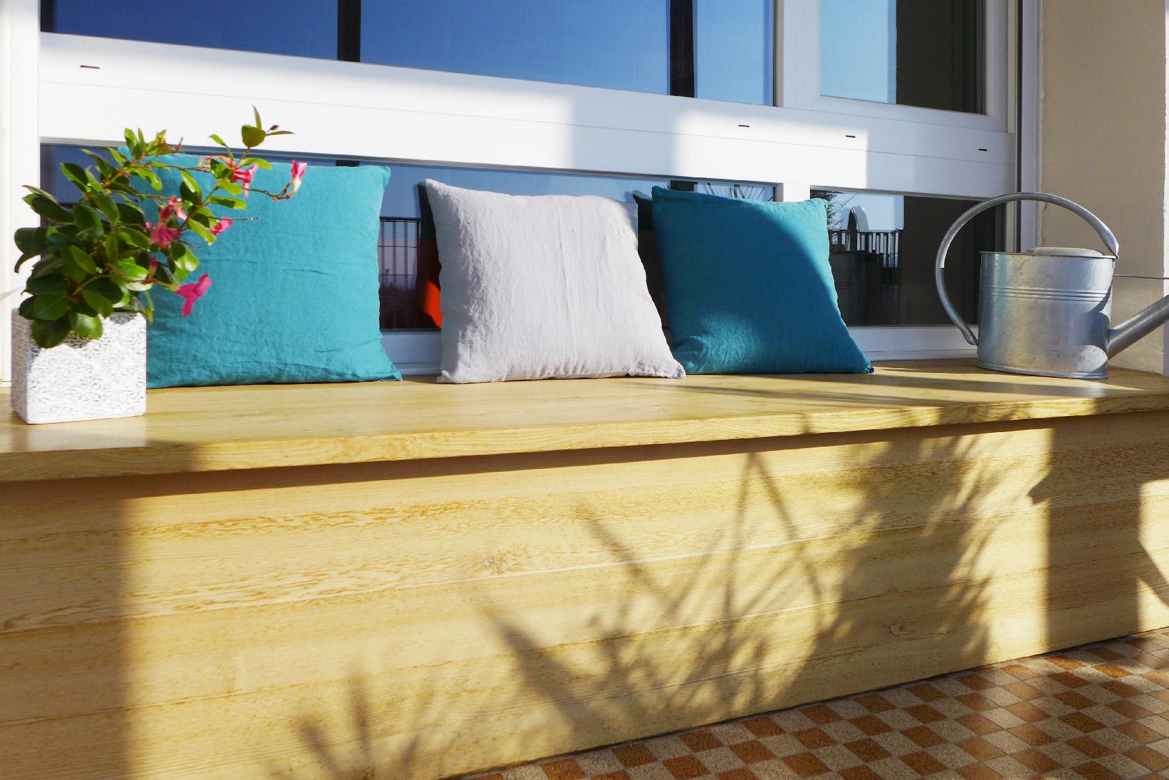 Une banquette en bois prend place devant les fenêtres, sur le balcon.