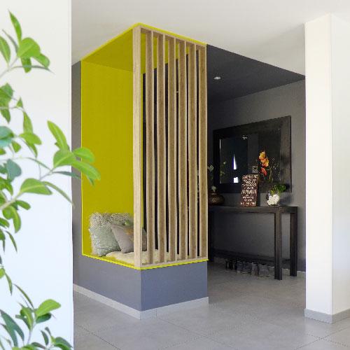 Réalisation du studio d'architecture et de décoration Skéa Designer. Vue d'une entrée avec banquette et rangement sur mesure. Séparation sous forme de claustra.