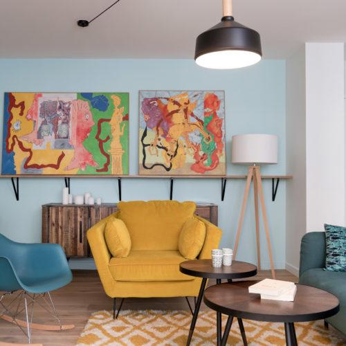 Réalisation du studio d'architecture et de décoration Skéa Designer. Le petit salon est quant à lui très coloré avec son canapé bleu canard et son fauteuil jaune.